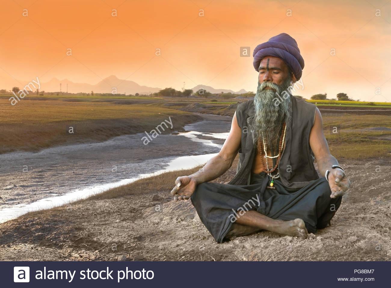 Indian Sadhu meditation at bank of river - Stock Image