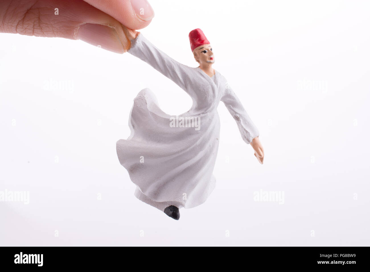 Hand holding a Sufi Derviş on a white background - Stock Image