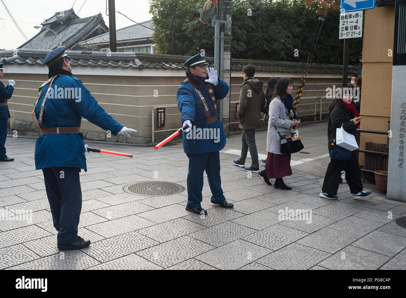 23.12.2017, Kyoto, Japan, Asia - Traffic wardens are seen regulating the flow of traffic at an intersection in Kyoto's old city. - Stock Image