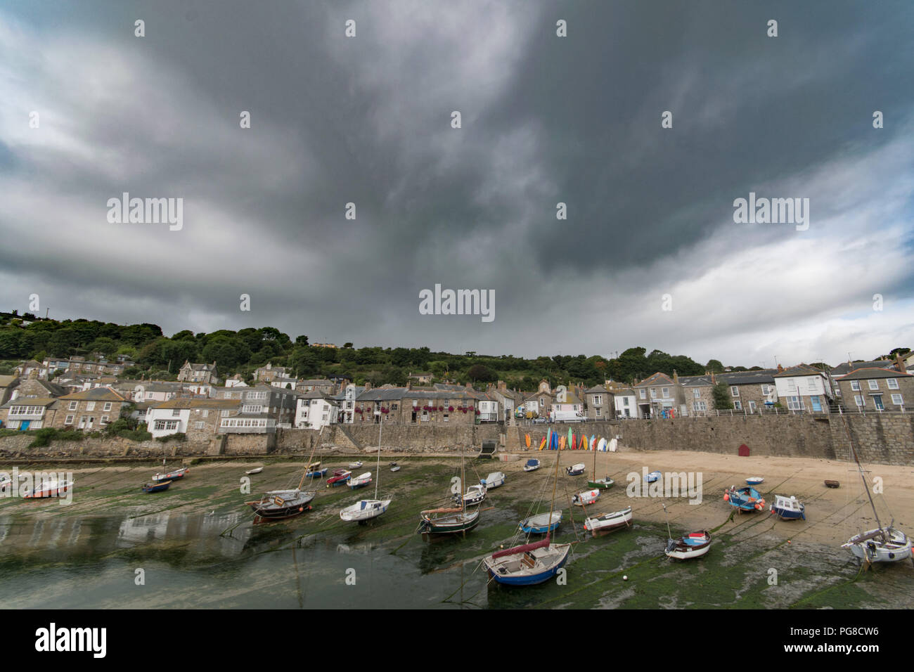Mousehole, Cornwall, UK. 24th August 2018. UK Weather. It was Yo-yo weather this morning with alternating bright sunshine then heavy downpours at Moushehole, which is a popular bank holiday destination from people around the UK and Europe. Credit: Simon Maycock/Alamy Live News Stock Photo