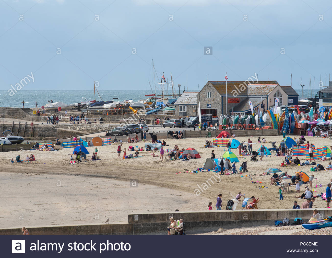 Lyme Regis, Dorset, UK. 24th August 2018.  UK Weather: Visitors enjoy bright sunny spells and a fresh breeze at the beach at Lyme Regis at the start of the Bank Holiday weekend.  Cooler, cloudier conditions are expected with some showery outbreaks. Credit: Celia McMahon/Alamy Live News - Stock Image