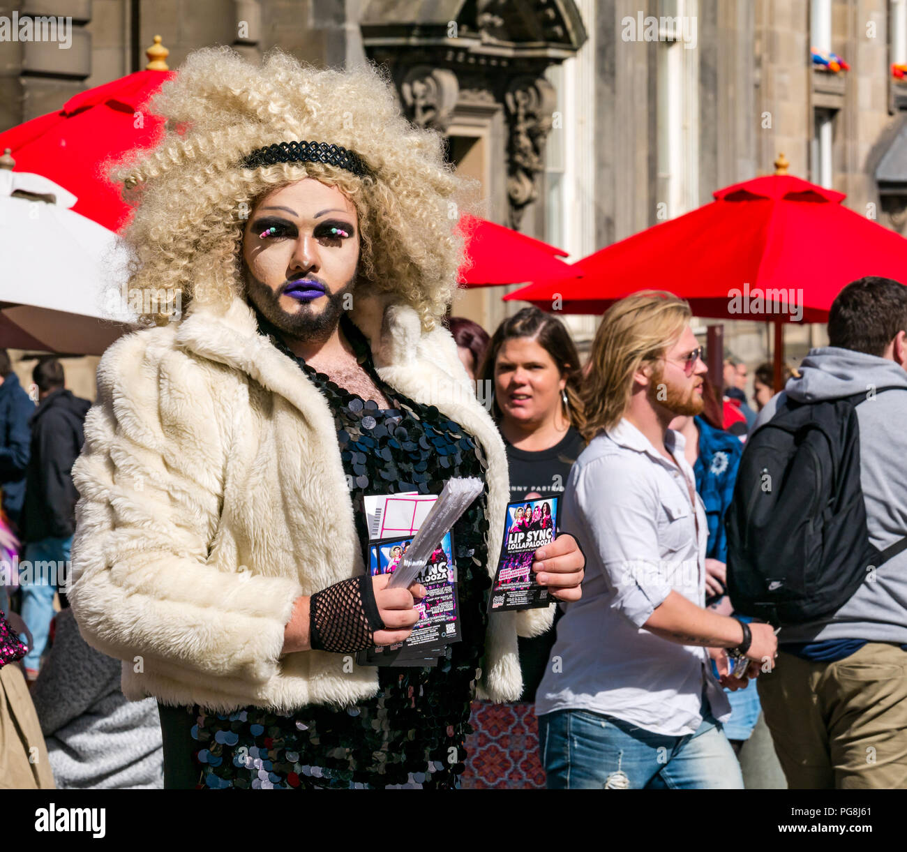 Edinburgh Fringe Festival,, Edinburgh, Scotland, UK. 24th August 2018.  The sun shines on Fringe goers and a festival performer at the Virgin Money sponsored street venue on the Royal Mile. A man wearing make up, a blonde wig and a fur coat in drag queen costume handing out flyers for his Fringe show called Lip Sync Lollapalooza - Stock Image