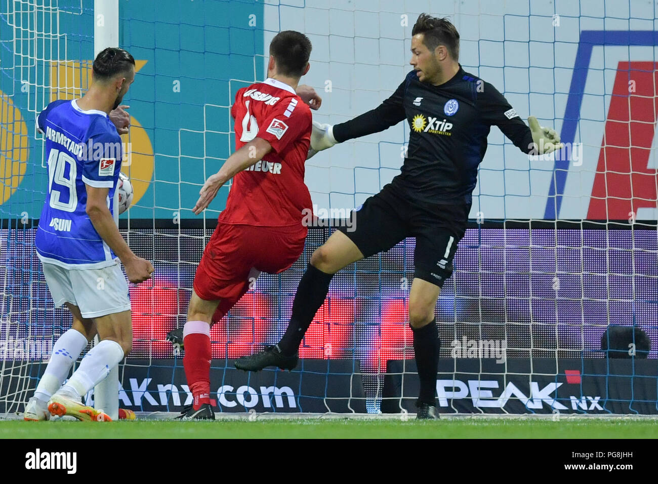 Darmstadt, Germany. 24th Aug, 2018. Soccer, 2nd Bundesliga, Darmstadt 98 vs MSV Duisburg, 3rd Matchday, at the Merck Stadium at Boellenfalltor. Darmstadt's Serdar Dursun (L) scores the 2-0 goal passing Duisburg goalkeeper Daniel Davari (R) and defender Dustin Bomheuer. Credit: Uwe Anspach/dpa - IMPORTANT NOTICE: DFL regulations prohibit any use of photographs as image sequences and/or quasi-video./dpa/Alamy Live News - Stock Image