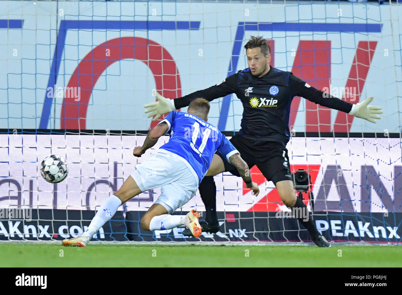 Darmstadt, Germany. 24th Aug, 2018. Soccer, 2nd Bundesliga, Darmstadt 98 vs MSV Duisburg, 3rd Matchday, at the Merck Stadium at Boellenfalltor. Darmstadt's Tobias Kempe (L) scores the 3-0 goal past Duisburg goalkeeper Daniel Davari. Credit: Uwe Anspach/dpa - IMPORTANT NOTICE: DFL regulations prohibit any use of photographs as image sequences and/or quasi-video./dpa/Alamy Live News - Stock Image