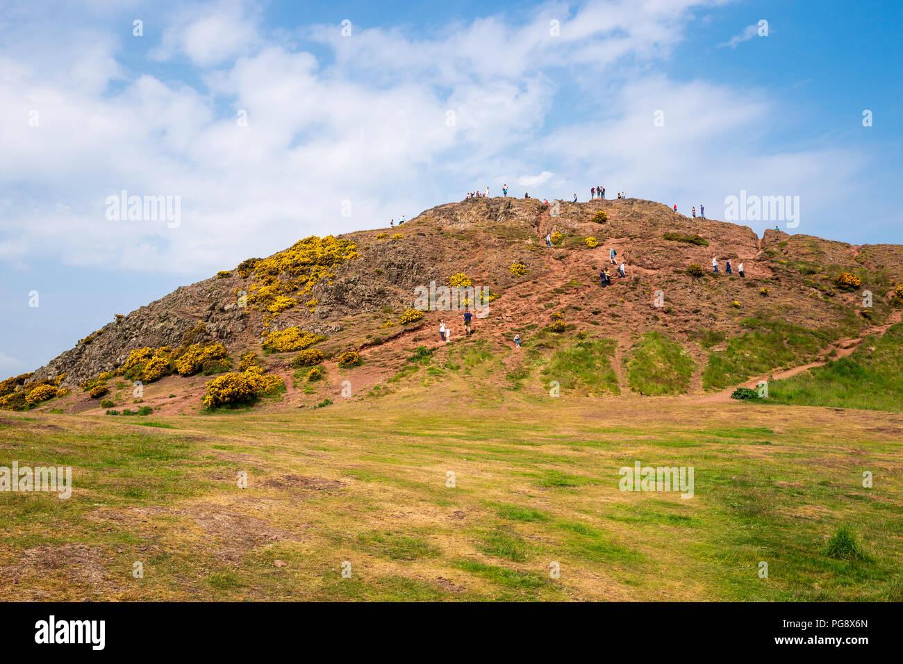 Tourists and walkers enjoy the summit of Arthur's Seat in Holyrood Park, Edinburgh, Scotland, UK. - Stock Image