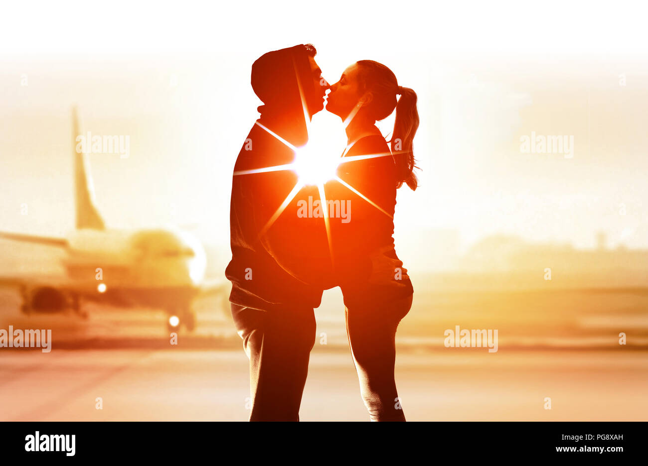 couple of young lovers in airport embrace and kiss each other - Stock Image