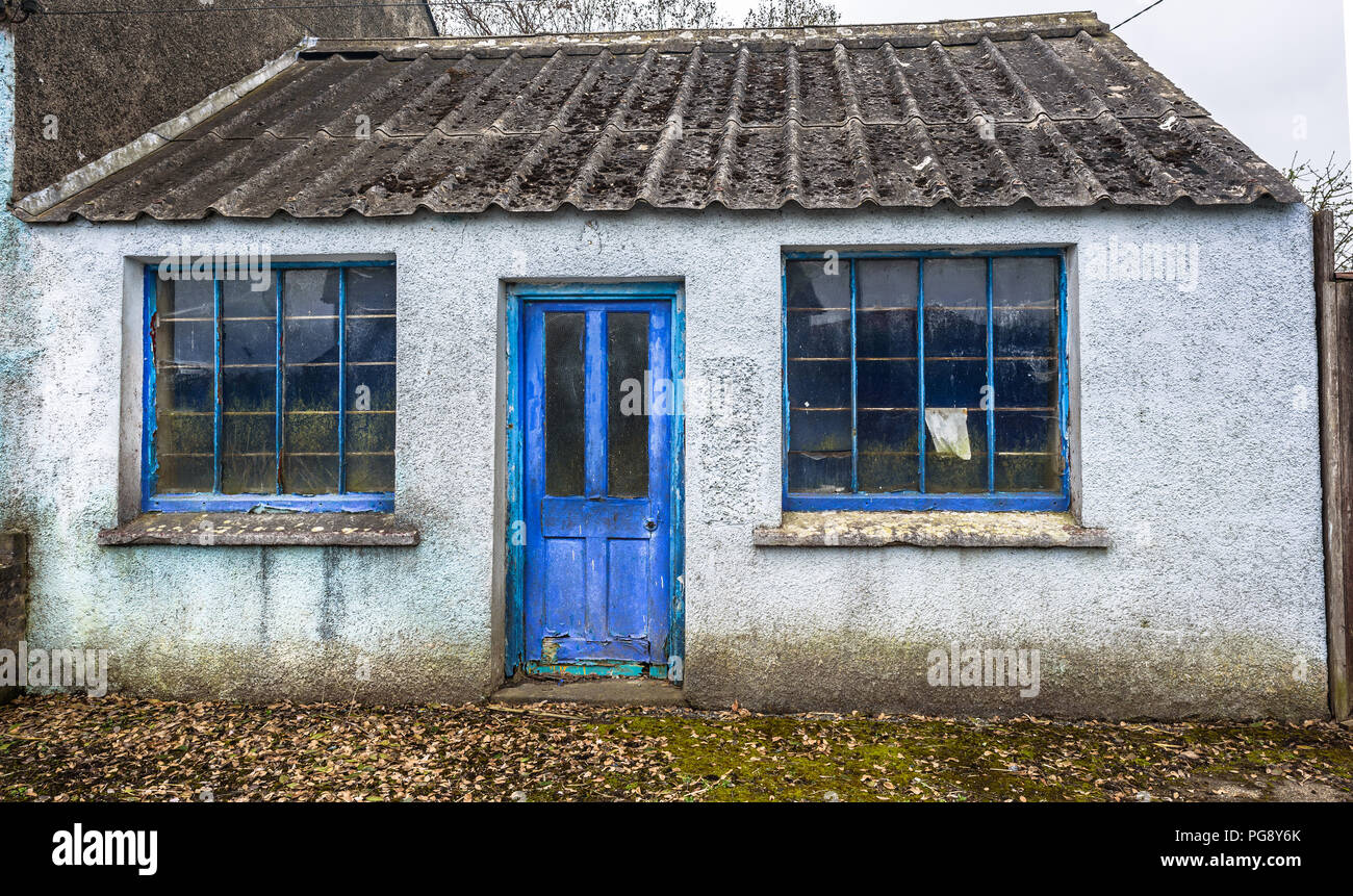 Old abandoned house with weathered window frames and door. - Stock Image