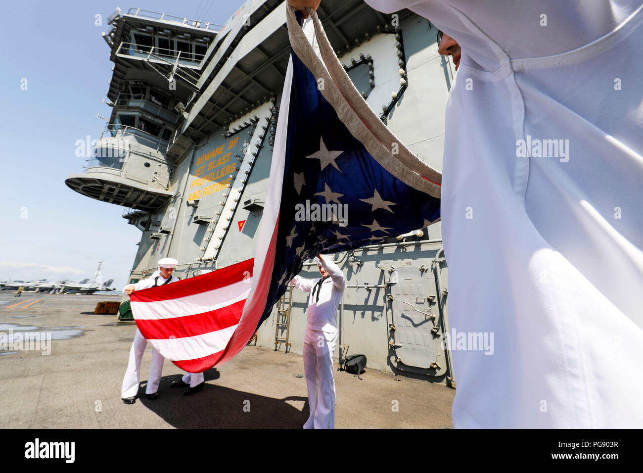 180819-N-FB291-1086 ATLANTIC OCEAN (Aug. 19, 2018) Sailors aboard the Nimitz-class aircraft carrier USS Abraham Lincoln (CVN 72) ceremoniously fold the national ensign. (U.S. Navy photo by Mass Communication Specialist 3rd Class Garrett LaBarge/Released) - Stock Image