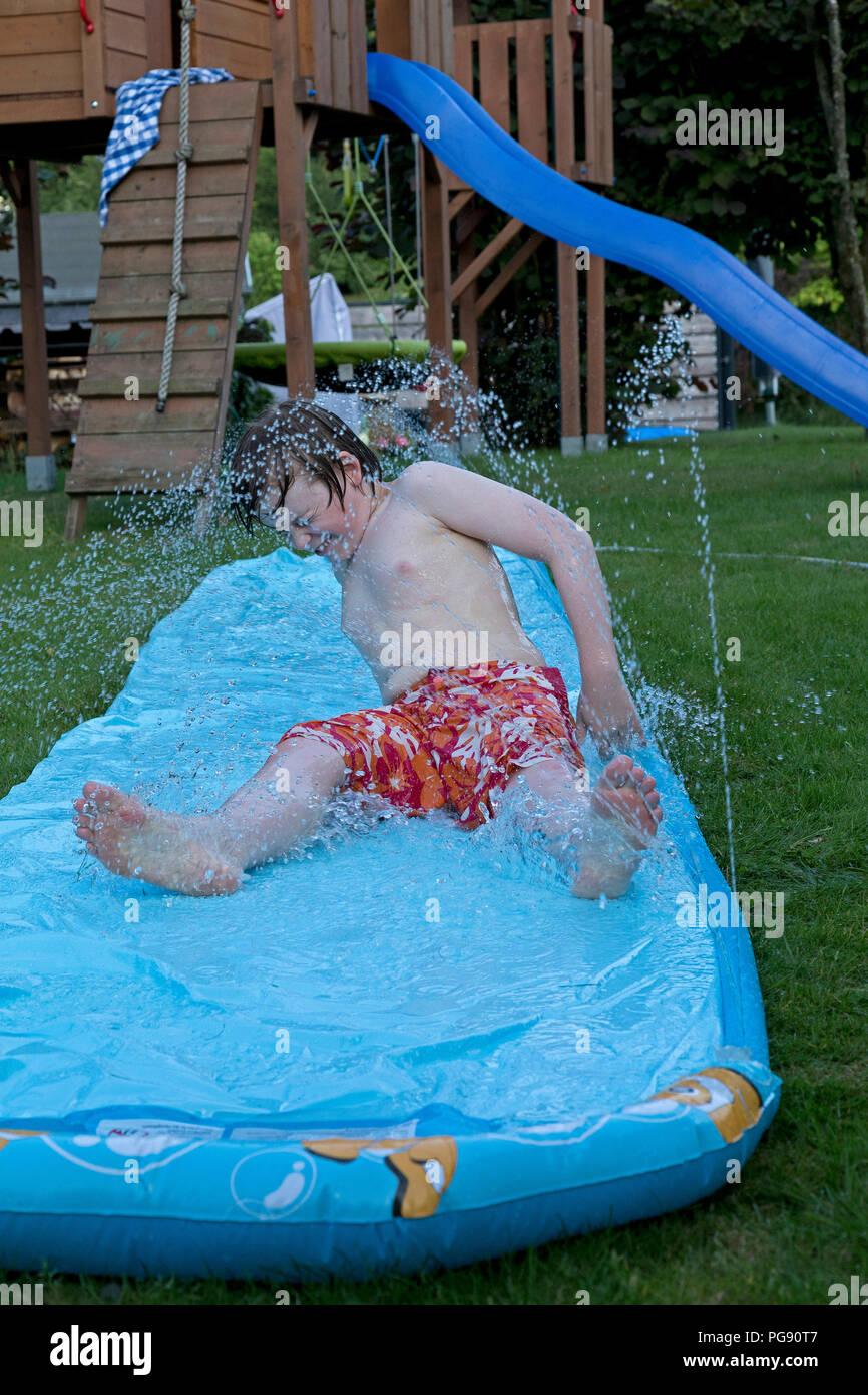 boy on water slide, Neuenkleusheim, Olpe, North Rhine-Westphalia, Germany - Stock Image