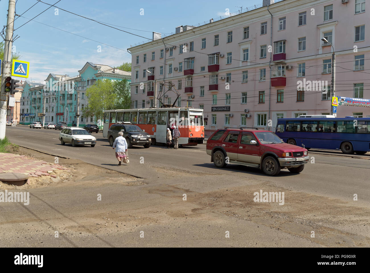 Komsomolsk-on-Amur, Russia - May 25, 2018: Old red tram on the rail station 'Hotel Voskhod' in the middle line of the street 'Prospekt Lenina' - Stock Image