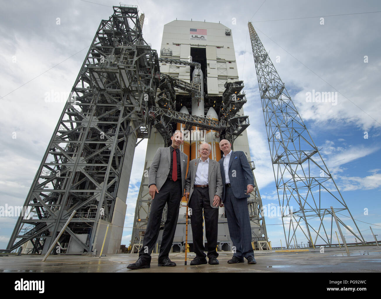 NASA Associate Administrator for the Science Mission Directorate Thomas Zurbuchen, left, American solar astrophysicist, and professor emeritus at the University of Chicago, Eugene Parker, center, and President and Chief Executive Officer for United Launch Alliance Tory Bruno pose for a group photo in front of  the ULA Delta IV Heavy rocket with NASA's Parker Solar onboard, Friday, Aug. 10, 2018, Launch Complex 37 at Cape Canaveral Air Force Station, Florida. This is the first NASA mission that has been named for a living individual. Parker Solar Probe is humanity's first-ever mission into a pa - Stock Image