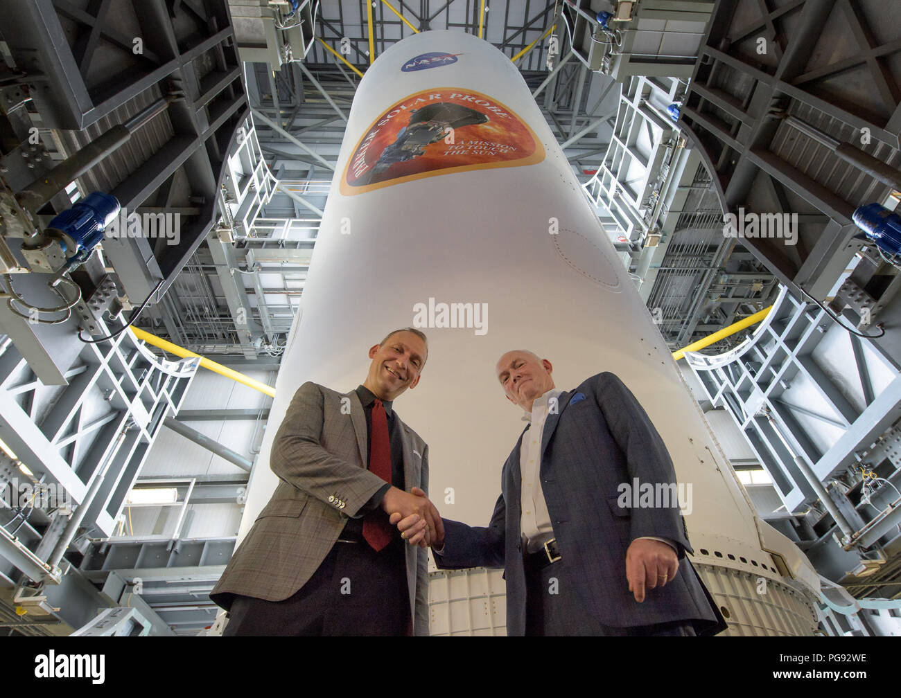 NASA Associate Administrator for the Science Mission Directorate Thomas Zurbuchen, left, and President and Chief Executive Officer for United Launch Alliance Tory Bruno shake hands after viewing the ULA Delta IV Heavy rocket with NASA's Parker Solar onboard, Friday, Aug. 10, 2018, Launch Complex 37 at Cape Canaveral Air Force Station, Florida. This is the first NASA mission that has been named for a living individual. Parker Solar Probe is humanity's first-ever mission into a part of the Sun's atmosphere called the corona.  Here it will directly explore solar processes that are key to understa - Stock Image
