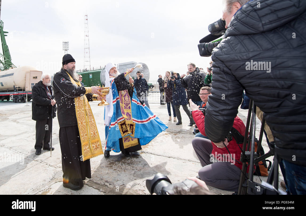 An Orthodox Priest blesses members of the media at the Baikonur Cosmodrome launch pad, Tuesday, March 20, 2018 in Baikonur, Kazakhstan. Expedition 55 Soyuz Commander Oleg Artemyev of Roscosmos, Ricky Arnold and Drew Feustel of NASA are scheduled to launch to the International Space Station aboard the Soyuz MS-08 spacecraft on Wednesday, March, 21. - Stock Image