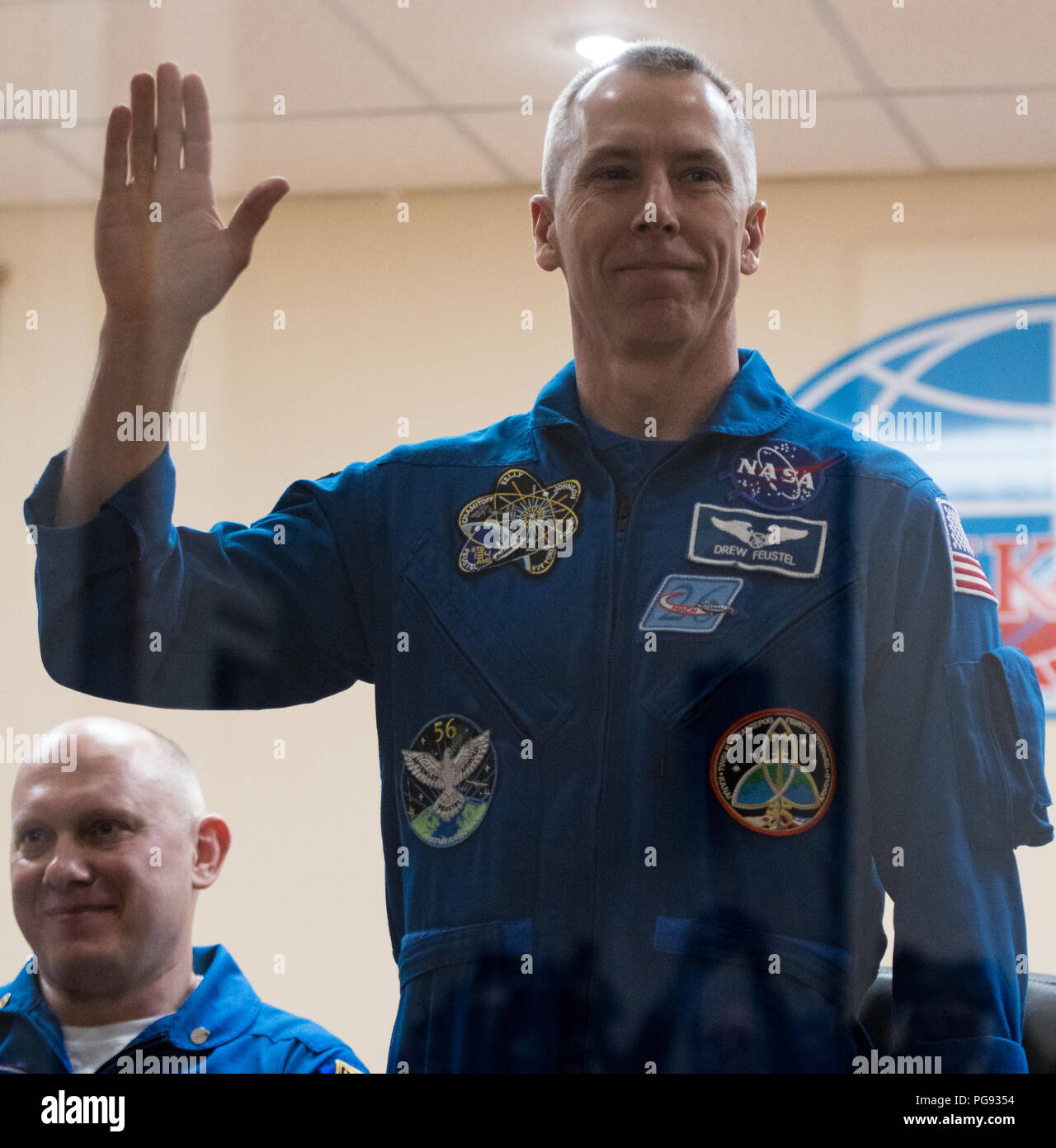 Expedition 55 flight engineer Drew Feustel is seen in quarantine, behind glass, during a press conference, Tuesday, March 20, 2018 at the Cosmonaut Hotel in Baikonur, Kazakhstan. Feustel, Soyuz Commander Oleg Artemyev of Roscosmos, and flight engineer Ricky Arnold of NASA are scheduled to launch to the International Space Station aboard the Soyuz MS-08 spacecraft on Wednesday, March, 21. - Stock Image