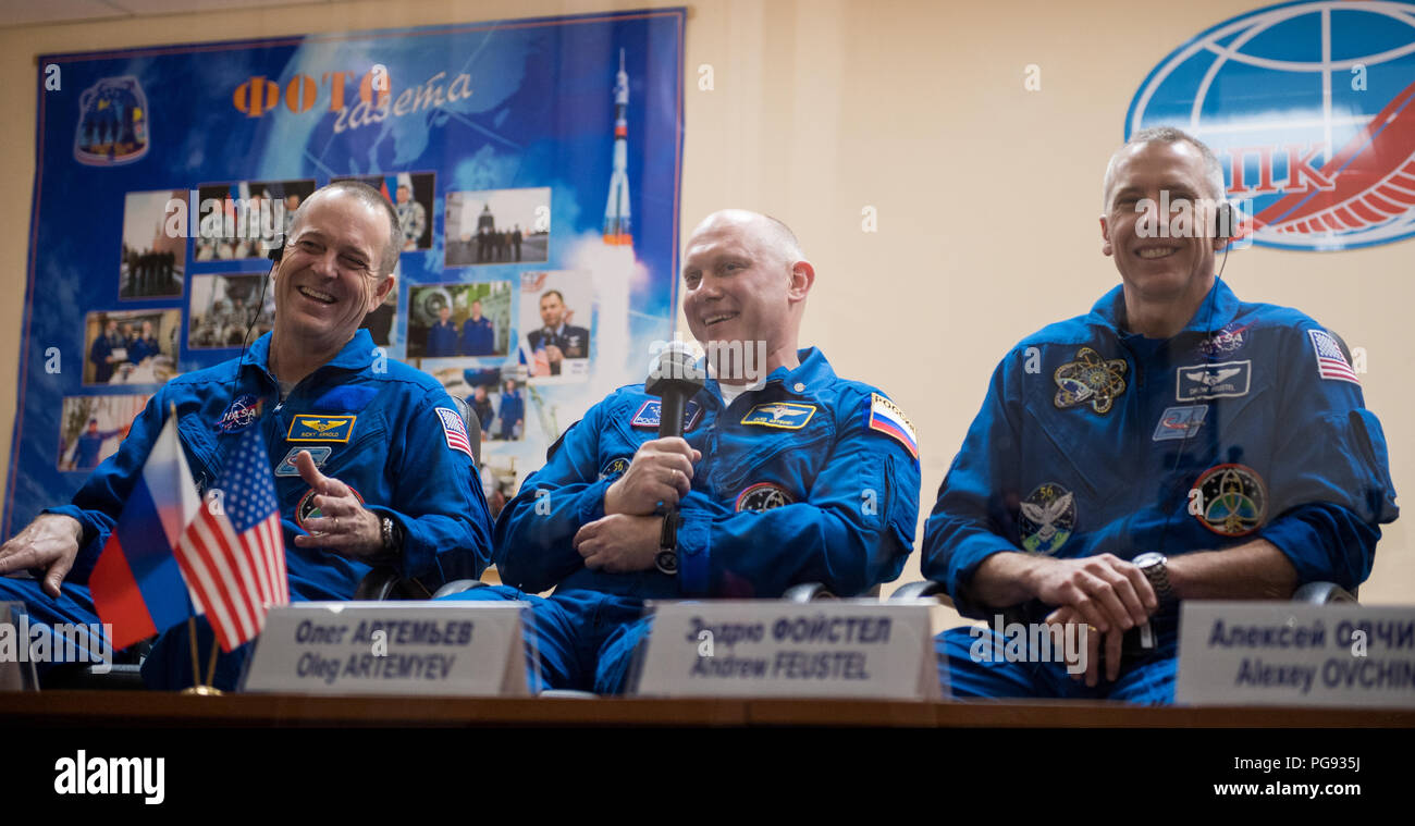 Expedition 55 prime crew members Ricky Arnold of NASA, left, Oleg Artemyev of Roscosmos, center, and Drew Feustel of NASA, right, are seen in quarantine, behind glass, during a press conference, Tuesday, March 20, 2018 at the Cosmonaut Hotel in Baikonur, Kazakhstan. Expedition 55 Soyuz Commander Oleg Artemyev of Roscosmos, Ricky Arnold and Drew Feustel of NASA are scheduled to launch to the International Space Station aboard the Soyuz MS-08 spacecraft on Wednesday, March, 21. - Stock Image