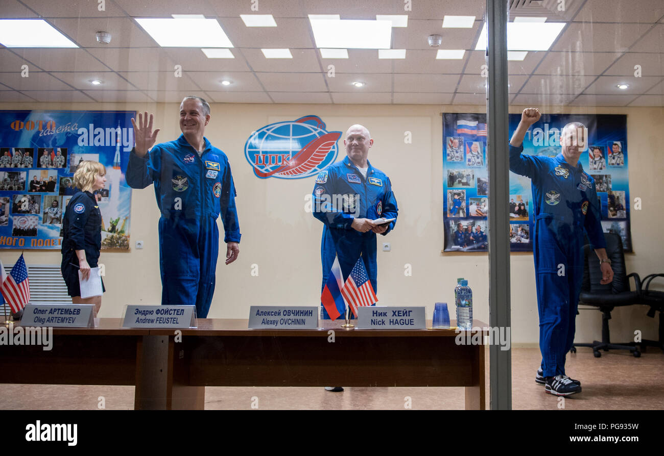 Expedition 55 flight engineer Ricky Arnold of NASA, left, Soyuz Commander Oleg Artemyev of Roscosmos, center, and flight engineer Drew Feustel of NASA, right, are seen at the conclusion of a press conference, Tuesday, March 20, 2018 at the Cosmonaut Hotel in Baikonur, Kazakhstan. Arnold, Artemyev, and Feustel are scheduled to launch to the International Space Station aboard the Soyuz MS-08 spacecraft on Wednesday, March, 21. - Stock Image