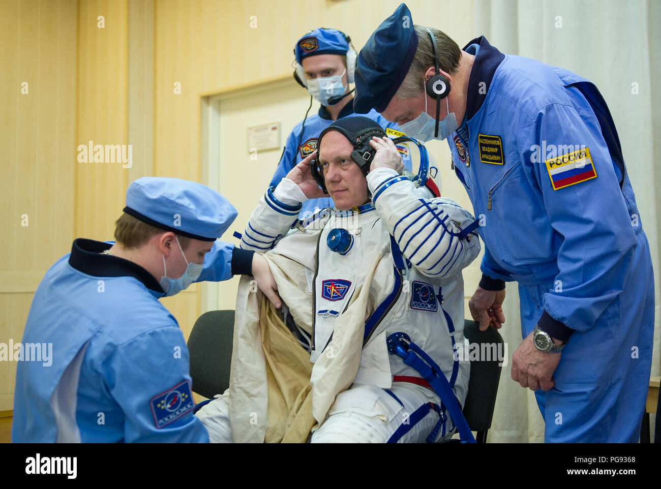 Expedition 55 Soyuz Commander Oleg Artemyev of Roscosmos is helped into his Russian Sokol suit as he and fellow crewmates, flight engineers Ricky Arnold and Drew Feustel of NASA prepare for their Soyuz launch to the International Space Station, Wednesday, March 21, 2018 in Baikonur, Kazakhstan. Artemyev, Arnold, and Feustel launched aboard the Soyuz MS-08 spacecraft at 1:44 p.m. Eastern time (11:44 p.m. Baikonur time) on March 21 to begin their journey to the International Space Station. - Stock Image