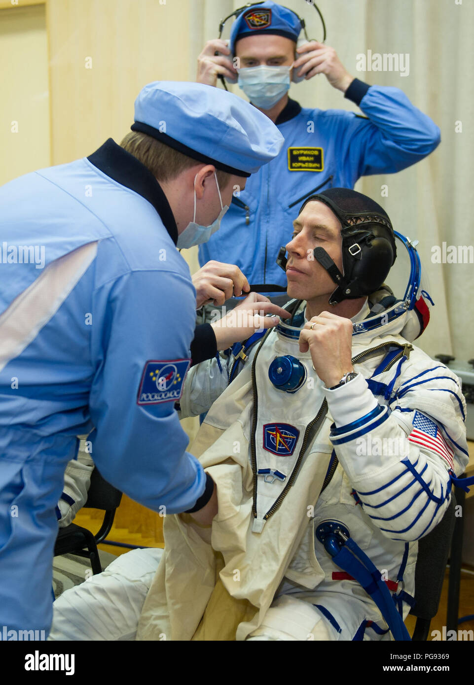 Expedition 55 flight engineer Drew Feustel of NASA is helped into his Russian Sokol suit as he and fellow crewmates, Soyuz Commander Oleg Artemyev of Roscosmos and Ricky Arnold of NASA prepare for their Soyuz launch to the International Space Station Wednesday, March 21, 2018 in Baikonur, Kazakhstan.  Feustel, Artemyev, and Arnold launched aboard the Soyuz MS-08 spacecraft at 1:44 p.m. Eastern time (11:44 p.m. Baikonur time) on March 21 to begin their journey to the International Space Station. - Stock Image