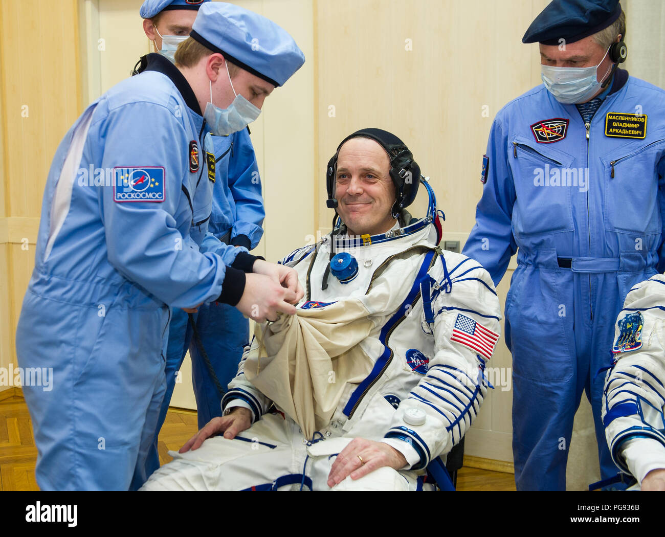 Expedition 55 flight engineer Ricky Arnold of NASA is helped into his Russian Sokol suit as he and fellow crewmates, Soyuz Commander Oleg Artemyev of Roscosmos and flight engineer Drew Feustel of NASA prepare for their Soyuz launch to the International Space Station Wednesday, March 21, 2018 in Baikonur, Kazakhstan. Arnold, Artemyev, and Feustel launched aboard the Soyuz MS-08 spacecraft at 1:44 p.m. Eastern time (11:44 p.m. Baikonur time) on March 21 to begin their journey to the International Space Station. - Stock Image