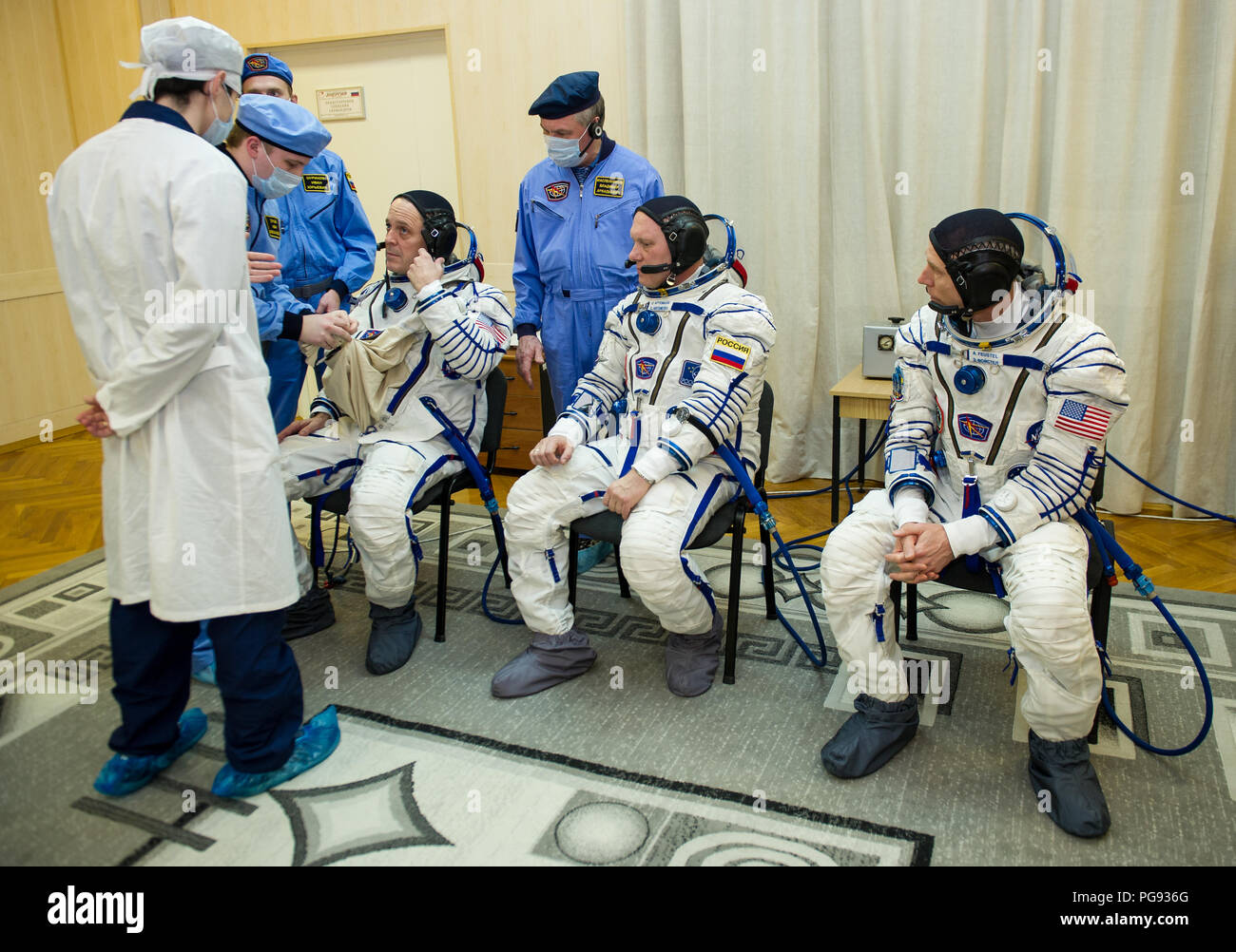 Expedition 55 flight engineer Ricky Arnold of NASA, left, is helped into his Russian Sokol suit as he and fellow crewmates, Soyuz Commander Oleg Artemyev of Roscosmos, center, and flight engineer Drew Feustel of NASA, right, prepare for their Soyuz launch to the International Space Station, Wednesday, March 21, 2018 in Baikonur, Kazakhstan. Arnold, Artemyev, and Feustel launched aboard the Soyuz MS-08 spacecraft at 1:44 p.m. Eastern time (11:44 p.m. Baikonur time) on March 21 to begin their journey to the International Space Station. - Stock Image