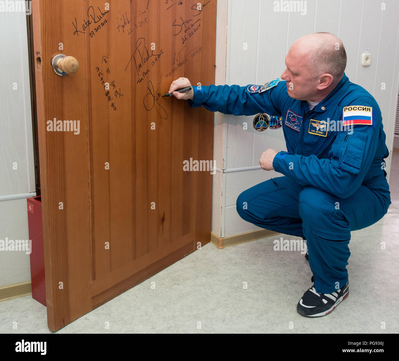 Expedition 55 Soyuz Commander Oleg Artemyev of Roscosmos performs the traditional door signing at the Cosmonaut Hotel prior to departing the hotel for launch on a Soyuz rocket with fellow crewmates Ricky Arnold and Drew Feustel of NASA, Wednesday, March 21, 2018 in Baikonur, Kazakhstan.  Artemyev, Arnold, and Feustel will launch in their Soyuz MS-08 spacecraft to the International Space Station to being a five month mission. - Stock Image