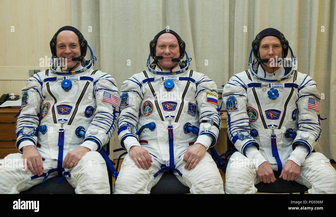 Expedition 55 flight engineer Ricky Arnold of NASA, left, Soyuz Commander Oleg Artemyev of Roscosmos, center, and flight engineer Drew Feustel of NASA, right, pose for a picture after donning their Russian Sokol suits as they prepare for their Soyuz launch to the International Space Station Wednesday, March 21, 2018 in Baikonur, Kazakhstan. Arnold, Artemyev, and Feustel launched aboard the Soyuz MS-08 spacecraft at 1:44 p.m. Eastern time (11:44 p.m. Baikonur time) on March 21 to begin their journey to the International Space Station. - Stock Image