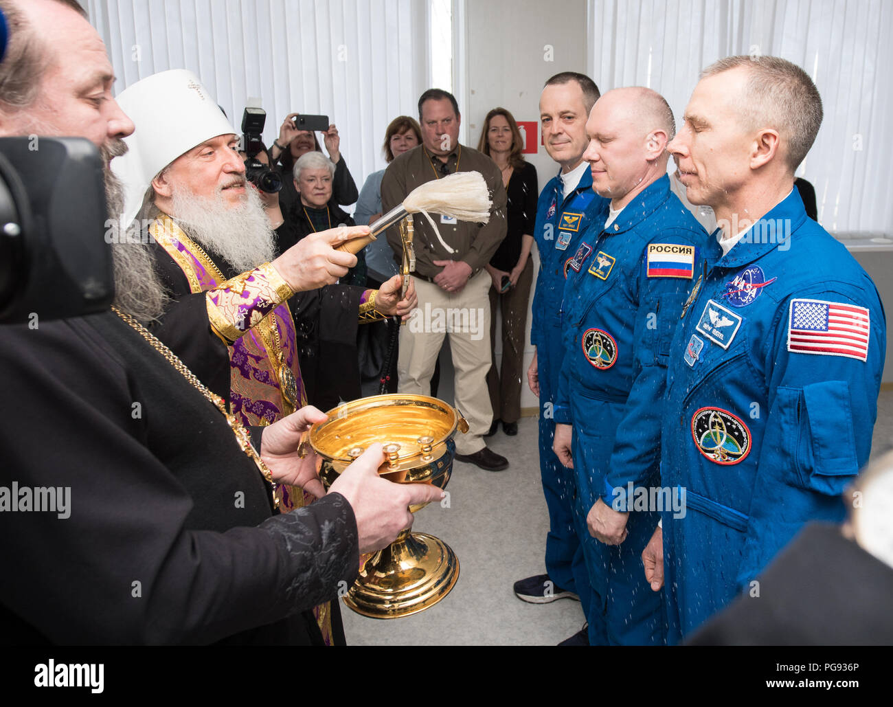 Expedition 55 flight engineer Ricky Arnold of NASA, Soyuz Commander Oleg Artemyev of Roscosmos, and flight engineer Drew Feustel of NASA receive a blessing from a Russian Orthodox Priest at the Cosmonaut Hotel prior to departing the hotel for launch on a Soyuz rocket, Wednesday, March 21, 2018 in Baikonur, Kazakhstan.  Arnold, Artemyev, and Feustel will launch in their Soyuz MS-08 spacecraft to the International Space Station to being a five month mission. - Stock Image