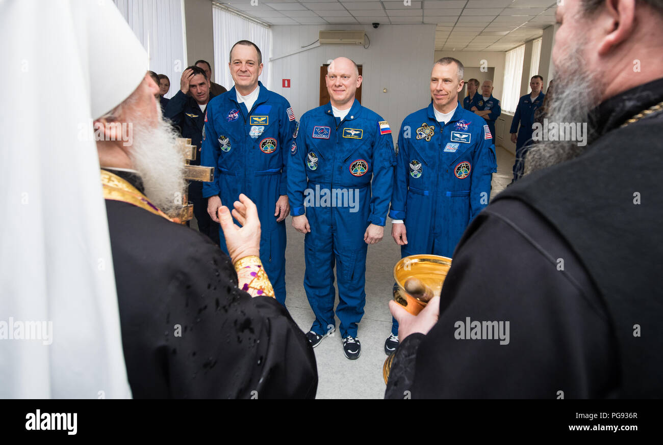 Expedition 55 flight engineer Ricky Arnold of NASA, left, Soyuz Commander Oleg Artemyev of Roscosmos, center, and flight engineer Drew Feustel, right, of NASA receive a blessing from a Russian Orthodox Priest at the Cosmonaut Hotel prior to departing the hotel for launch on a Soyuz rocket, Wednesday, March 21, 2018 in Baikonur, Kazakhstan.  Arnold, Artemyev, and Feustel will launch in their Soyuz MS-08 spacecraft to the International Space Station to being a five month mission. - Stock Image