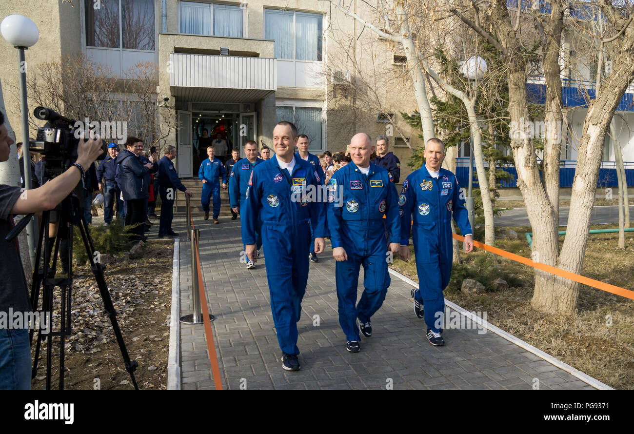 Expedition 55 flight engineer Ricky Arnold of NASA, left, Soyuz Commander Oleg Artemyev of Roscosmos, center, and flight engineer Drew Feustel of NASA, right, are seen as they depart the Cosmonaut Hotel to suit-up for their Soyuz launch to the International Space Station, Wednesday, March 21, 2018 in Baikonur, Kazakhstan. Launch of the Soyuz MS-08 is scheduled for 1:44 p.m. Eastern Time (11:44 p.m. Baikonur time) on March 21 and will send Arnold, Artemyev, and Feustel on a five month mission aboard the International Space Station. - Stock Image