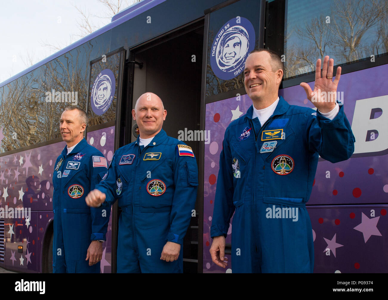Expedition 55 flight engineer Drew Feustel of NASA, left, Soyuz Commander Oleg Artemyev of Roscosmos, center, and flight engineer Ricky Arnold of NASA, right, wave farewell to family and friends as they depart the Cosmonaut Hotel to suit-up for their Soyuz launch to the International Space Station, Wednesday, March 21, 2018 in Baikonur, Kazakhstan. Launch of the Soyuz MS-08 is scheduled for 1:44 p.m. Eastern Time (11:44 p.m. Baikonur time) on March 21 and will send Feustel, Artemyev, and Arnold on a five month mission aboard the International Space Station. - Stock Image