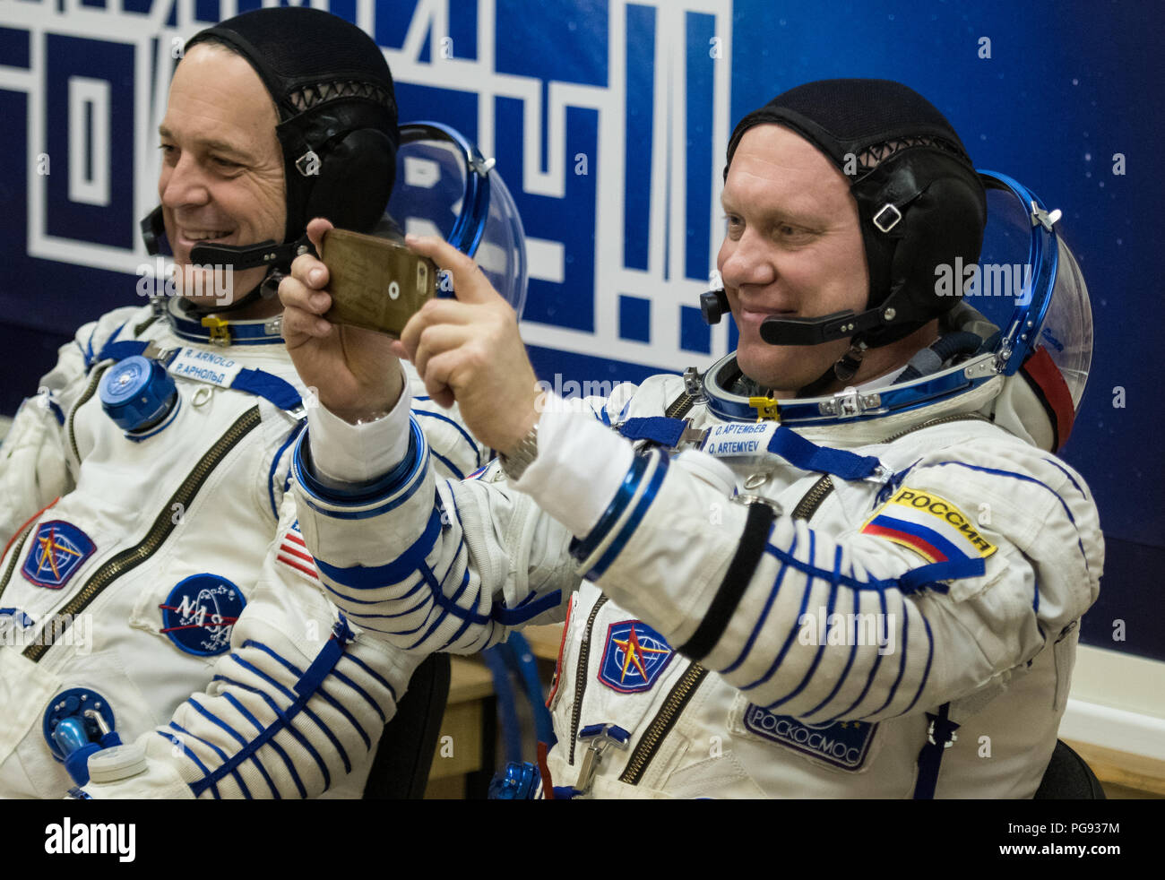 Expedition 55 Soyuz Commander Oleg Artemyev of Roscosmos takes a picture with a cell phone after having his Russian Sokol suit pressure checked in preparation for launch aboard the Soyuz MS-08 spacecraft, Wednesday, March 21, 2018 at the Baikonur Cosmodrome in Kazakhstan. Artemyev and flight engineers Ricky Arnold and Drew Feustel of NASA launched aboard the Soyuz MS-08 spacecraft at 1:44 p.m. Eastern time (11:44 p.m. Baikonur time) on March 21 to begin their journey to the International Space Station. - Stock Image