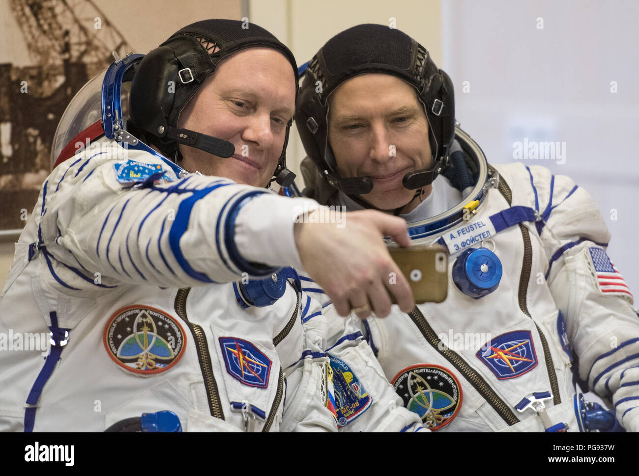 Expedition 55 Soyuz Commander Oleg Artemyev of Roscosmos, left, and flight engineer Drew Feustel of NASA take a selfie after having their Russian Sokol suits pressure checked in preparation for launch aboard the Soyuz MS-08 spacecraft, Wednesday, March 21, 2018 at the Baikonur Cosmodrome in Kazakhstan. Artemyev, Feustel, and flight engineer Ricky Arnold of NASA launched aboard the Soyuz MS-08 spacecraft at 1:44 p.m. Eastern time (11:44 p.m. Baikonur time) on March 21 to begin their journey to the International Space Station. - Stock Image