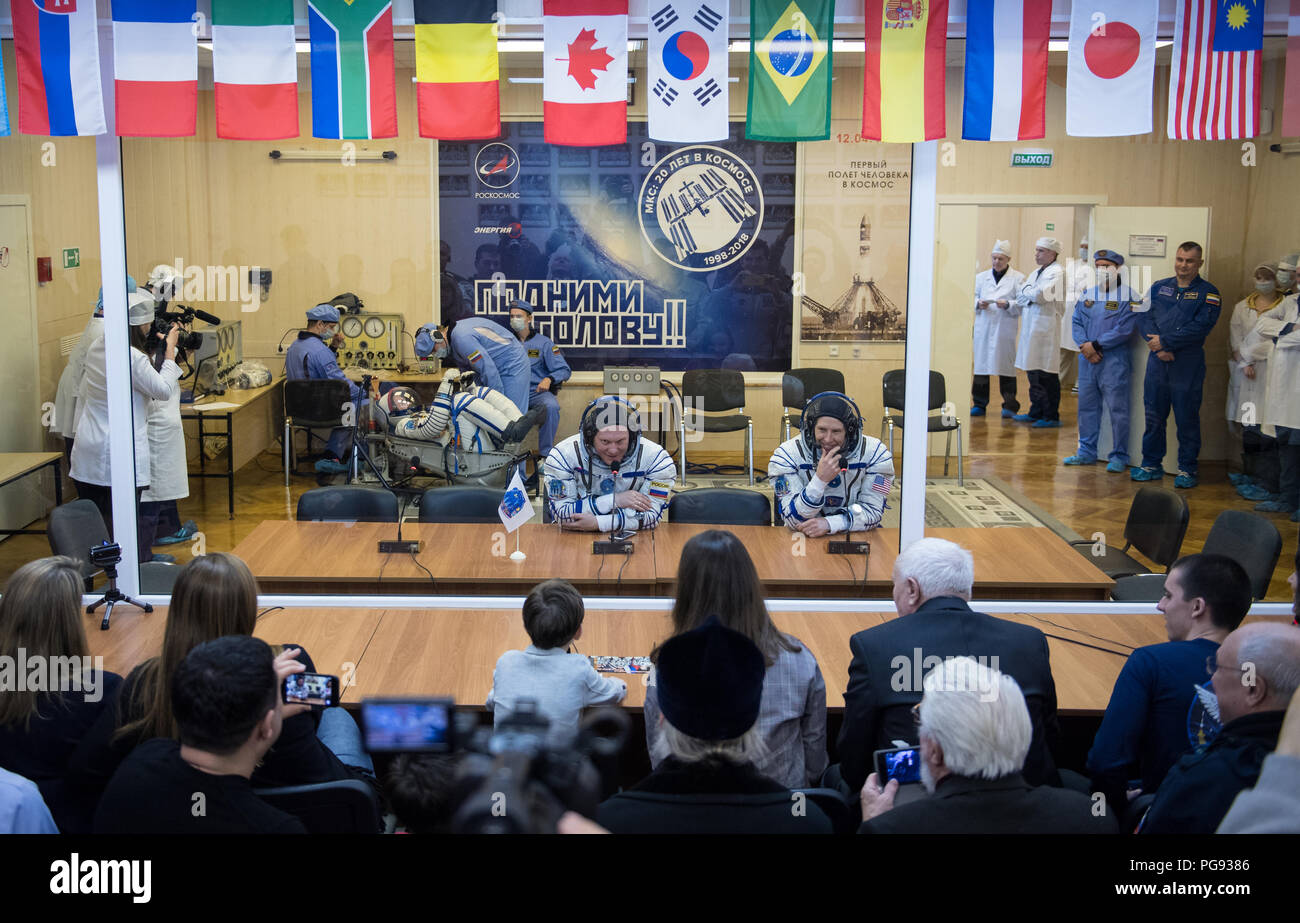Expedition 55 Soyuz Commander Oleg Artemyev of Roscosmos, left, and flight engineer Drew Feustel of NASA, right, talk with family and friends after having their Russian Sokol suits pressure checked in preparation for launch aboard the Soyuz MS-08 spacecraft, Wednesday, March 21, 2018 at the Baikonur Cosmodrome in Kazakhstan. Artemyev, Feustel, and flight engineer Ricky Arnold of NASA launched aboard the Soyuz MS-08 spacecraft at 1:44 p.m. Eastern time (11:44 p.m. Baikonur time) on March 21 to begin their journey to the International Space Station. - Stock Image