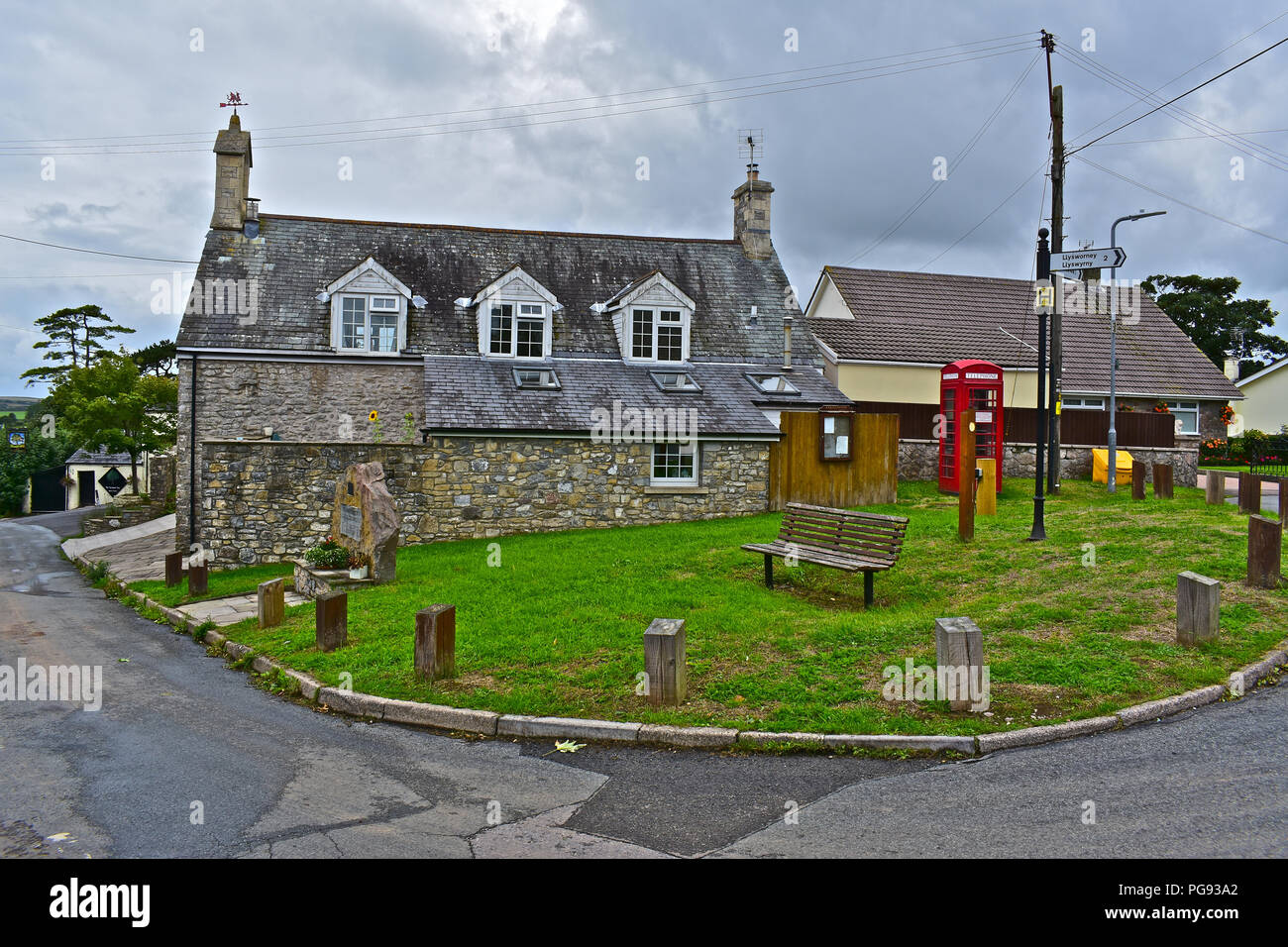 The 'green' in the middle of Colwinston in the Vale of Glamorgan S.Wales. Featuring old red telephone kiosk, former school building and war memorial. - Stock Image