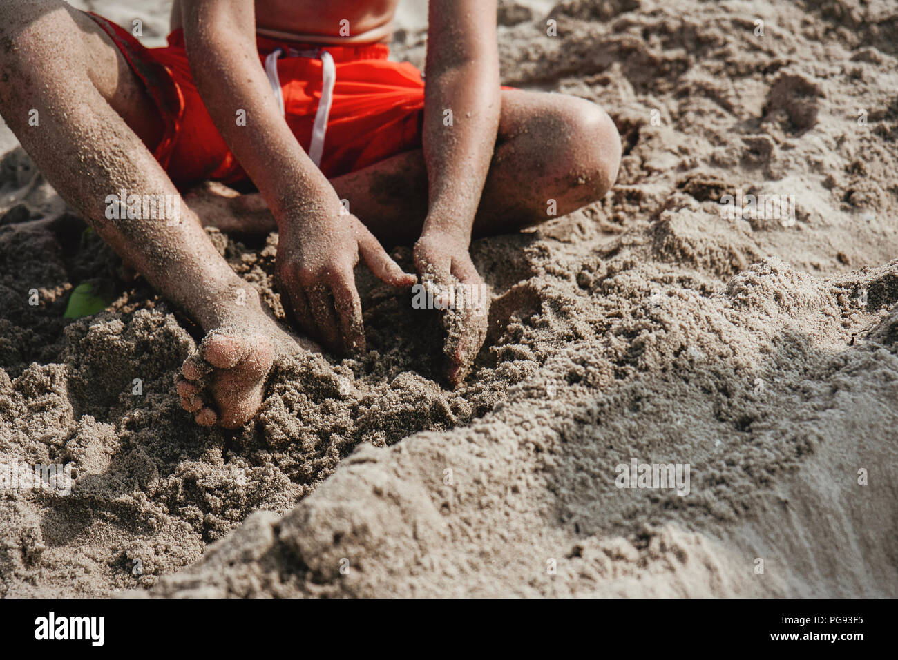 Young boy playing with sand at the beach. Close up of foot and hands, body parts. - Stock Image