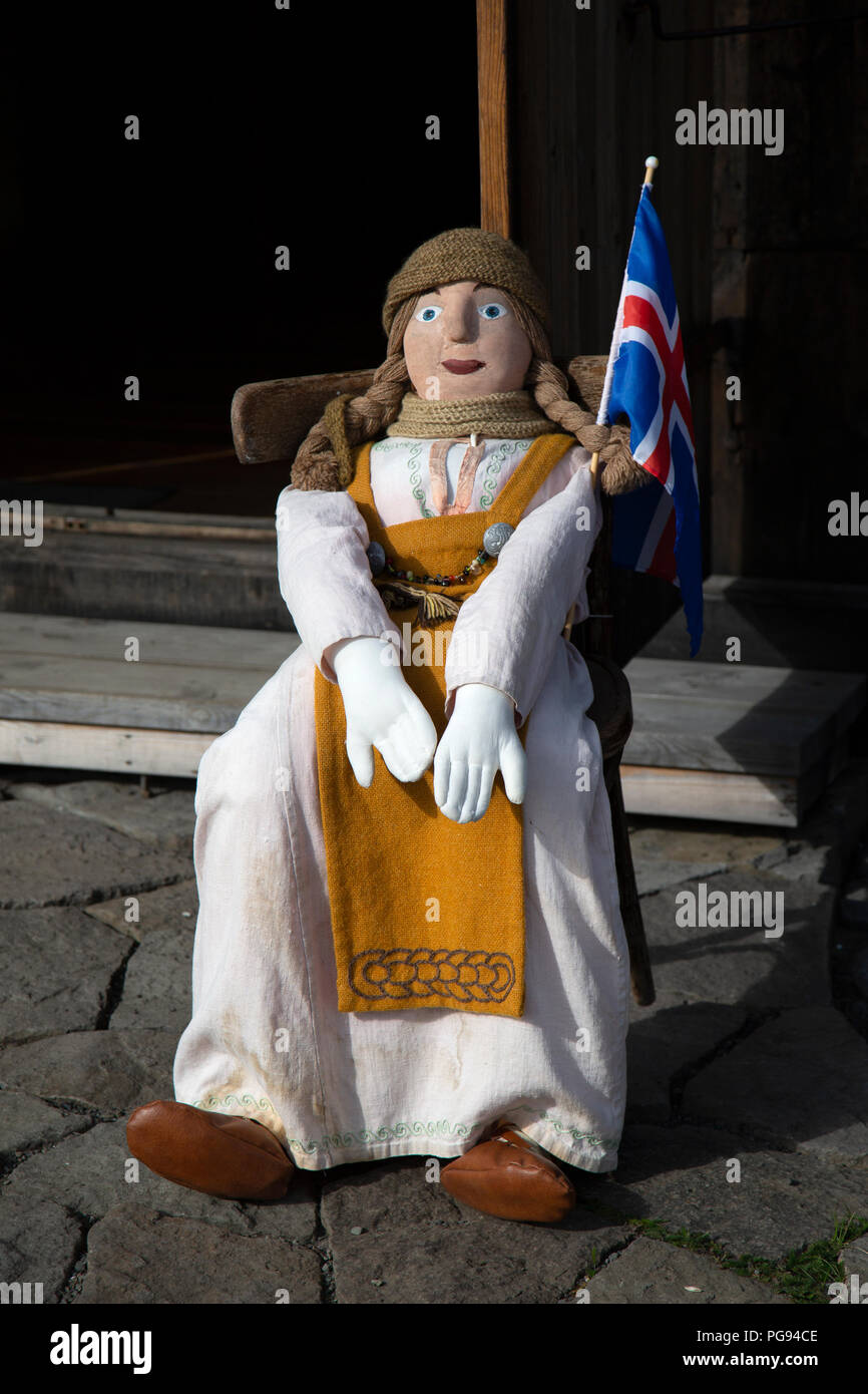 Life size doll, dressed in traditional Icelandic costume, sitting in a chair outside a museum in Iceland. - Stock Image