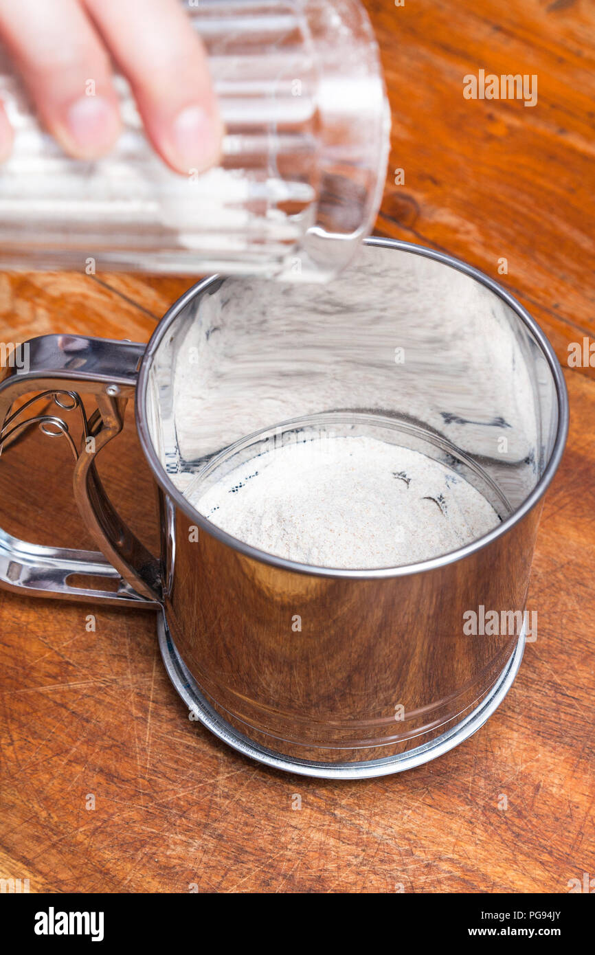 cooking of pie - pouring flour from glass into steel sifter - Stock Image
