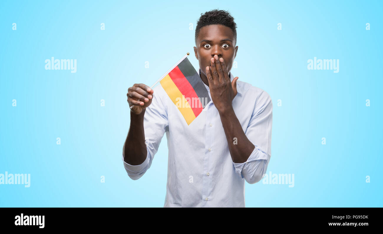 Young african american man holding german flag cover mouth with hand shocked with shame for mistake, expression of fear, scared in silence, secret con - Stock Image