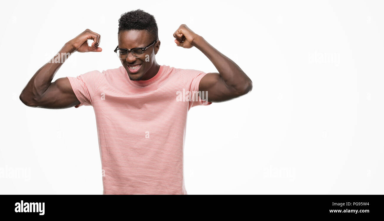 Young African American Man Wearing Pink T Shirt Showing Arms Muscles