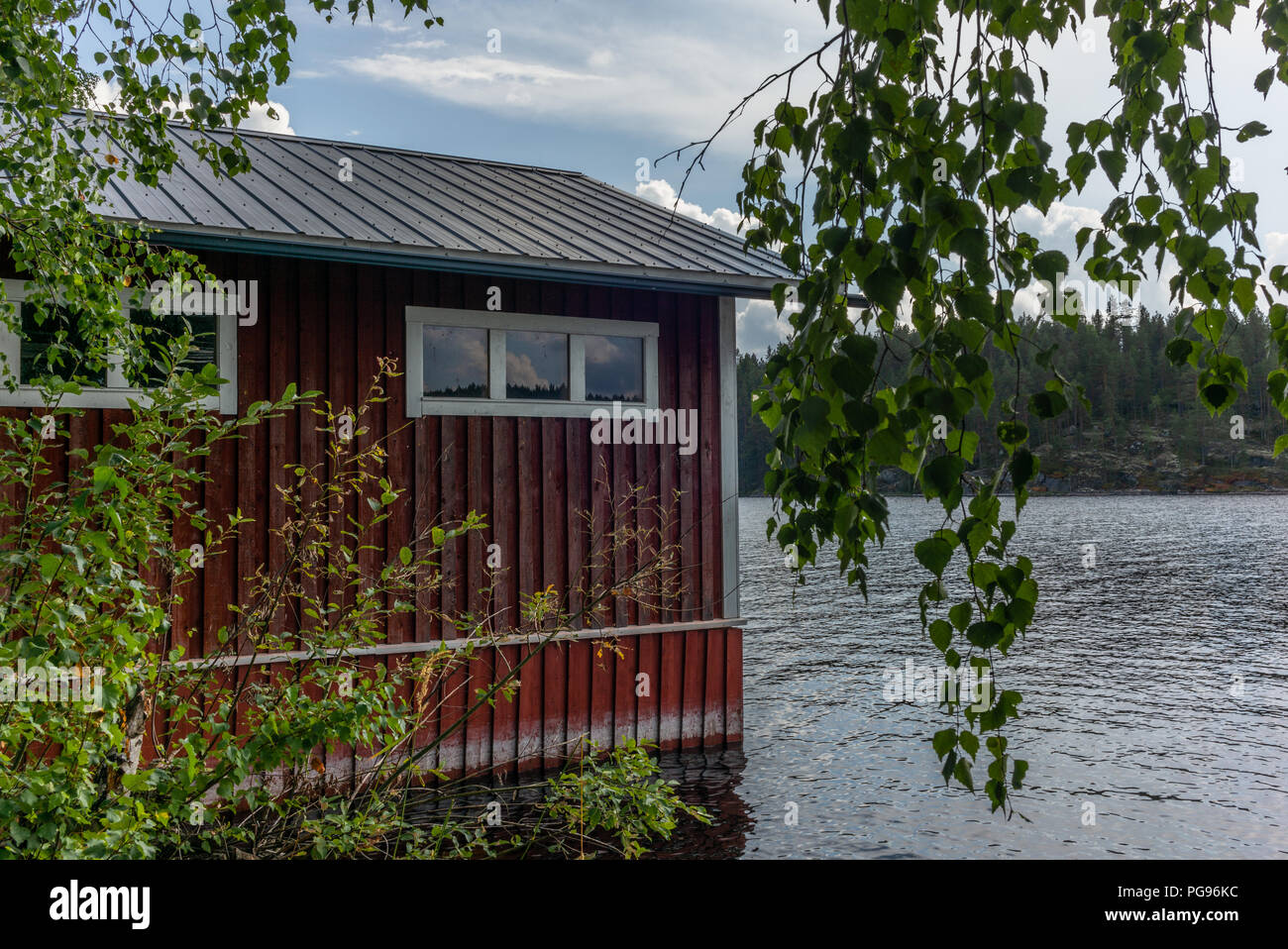 A typical red boat house  on the shore of the Saimaa lake in Finland - 2 Stock Photo