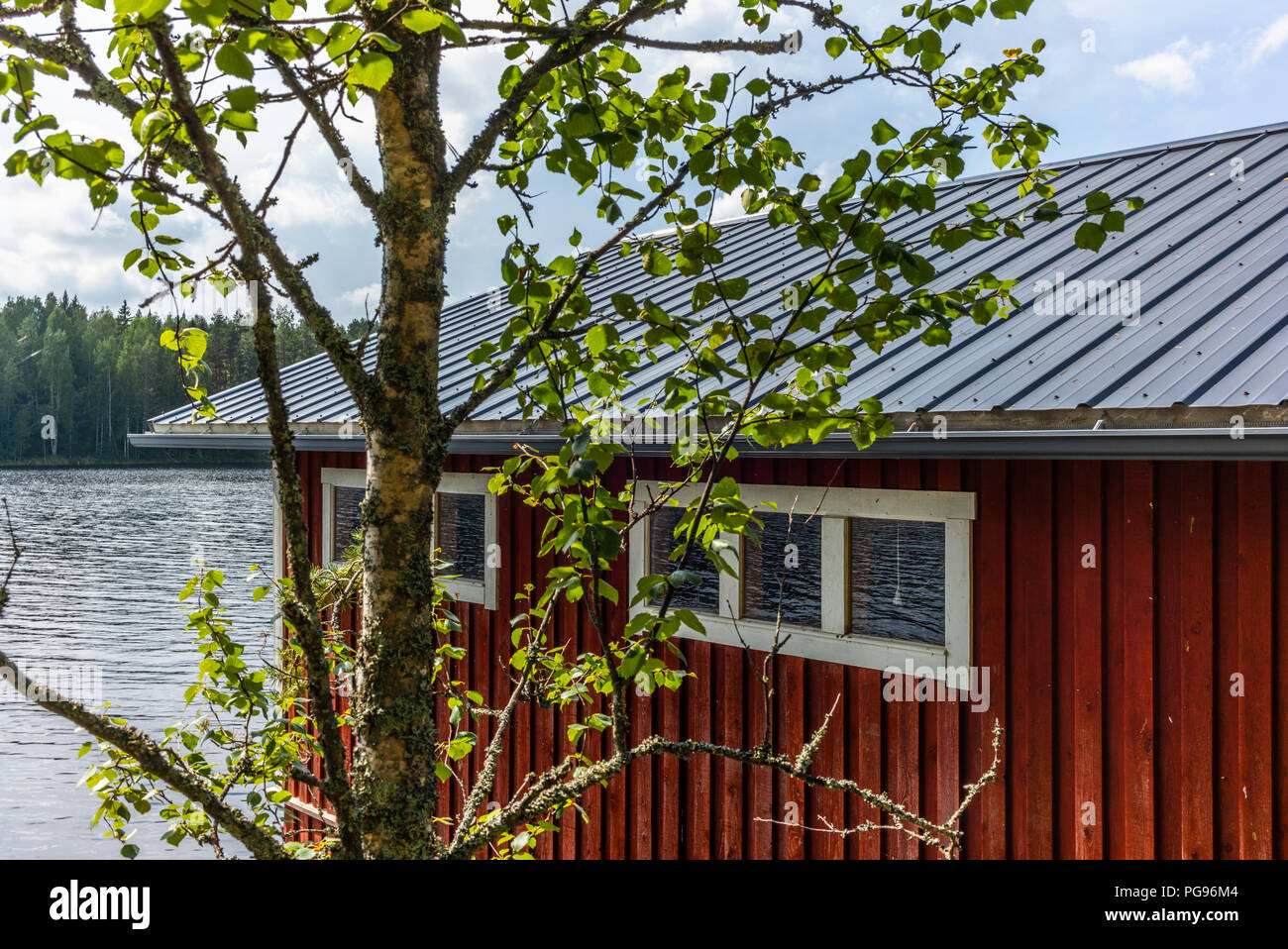 A typical red boat house  on the shore of the Saimaa lake in Finland - 8 Stock Photo