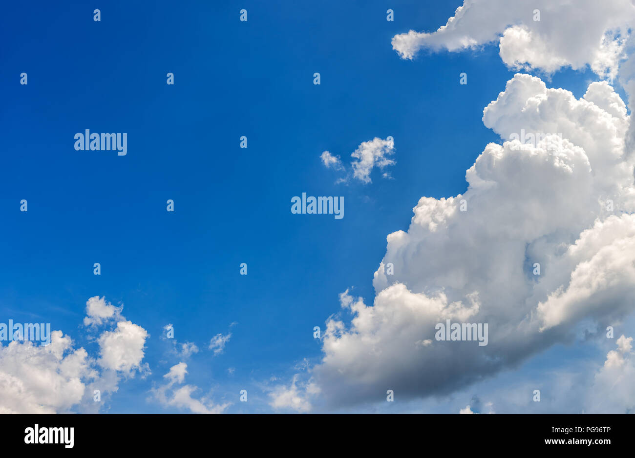 Landscape of a beautiful blue sky covered with cumulonimbus clouds on a warm summer afternoon - Stock Image