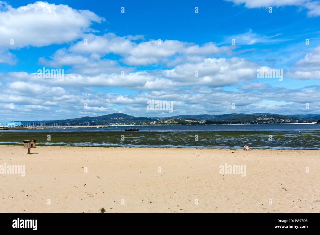 Woman alone taking the sunbath in Sada beach, Sada, A Coruña provints, Galicia, Spain - Stock Image