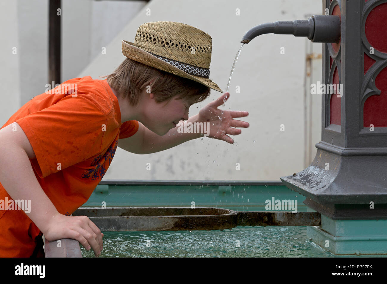 boy refreshing himself at a fountain, old town, Wangen, Allgaeu, Baden-Wuerttemberg, Germany - Stock Image