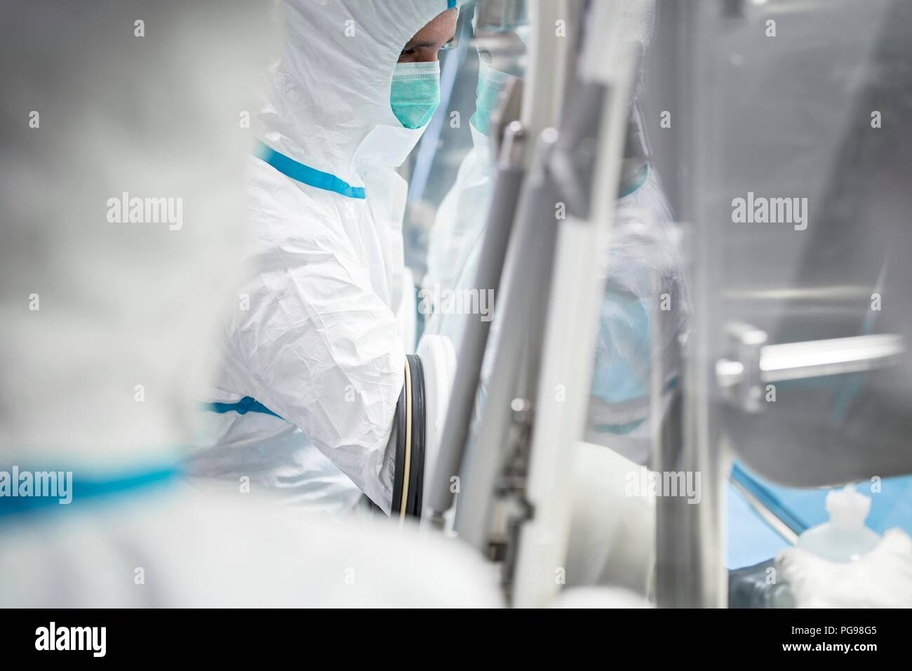 Technicians working in sealed, sterile isolator units in a laboratory that manufactures human tissues for implant. Such tissues include bone and skin grafts. - Stock Image