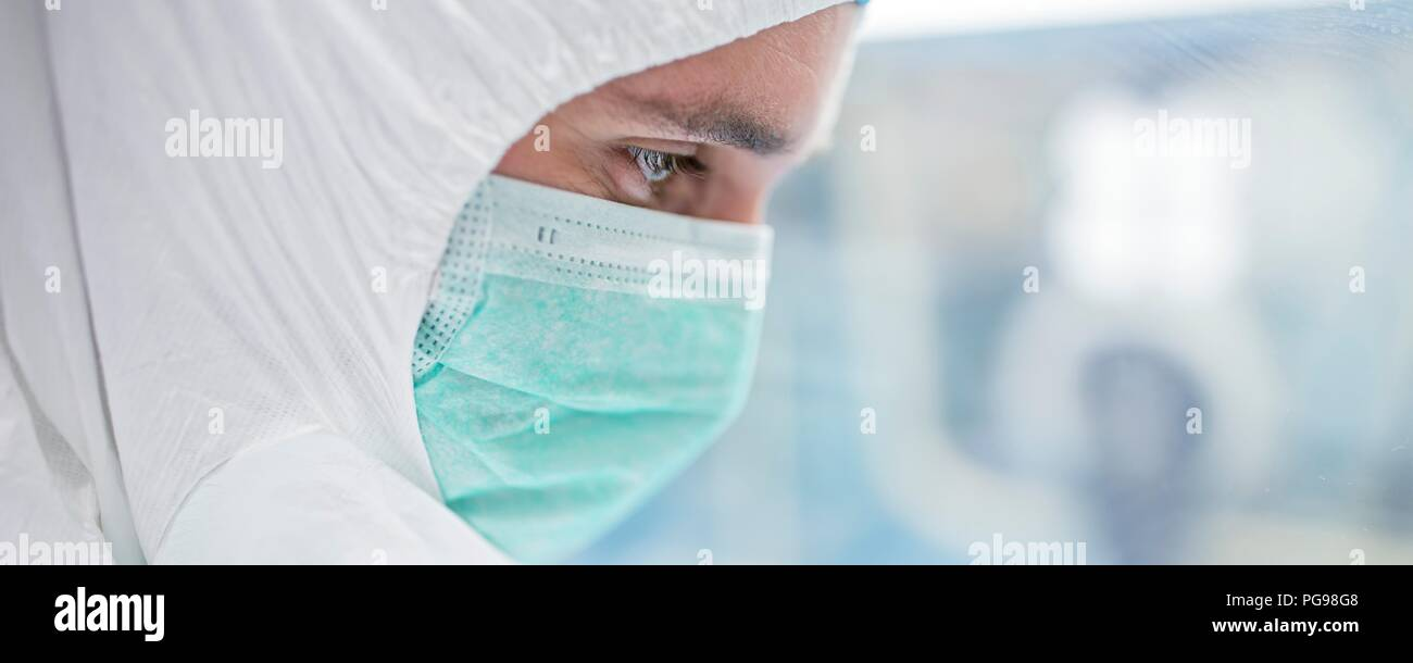 Close-up of a lab technician wearing a protective suit and face mask in a laboratory that must maintain a sterile environment. - Stock Image