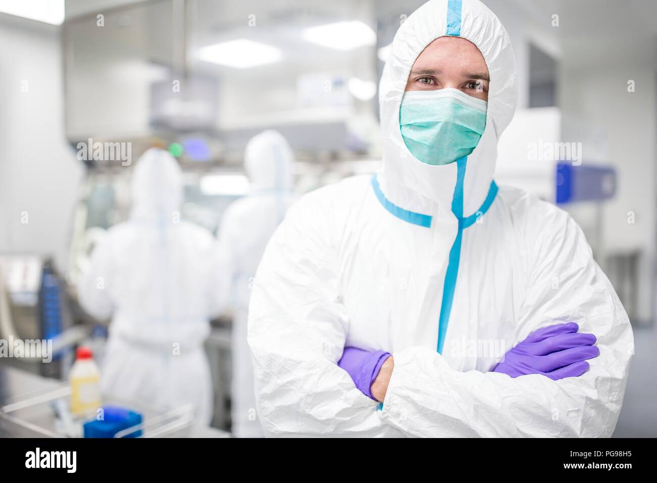 Lab technician wearing a protective suit and face mask in a laboratory that must maintain a sterile environment. - Stock Image