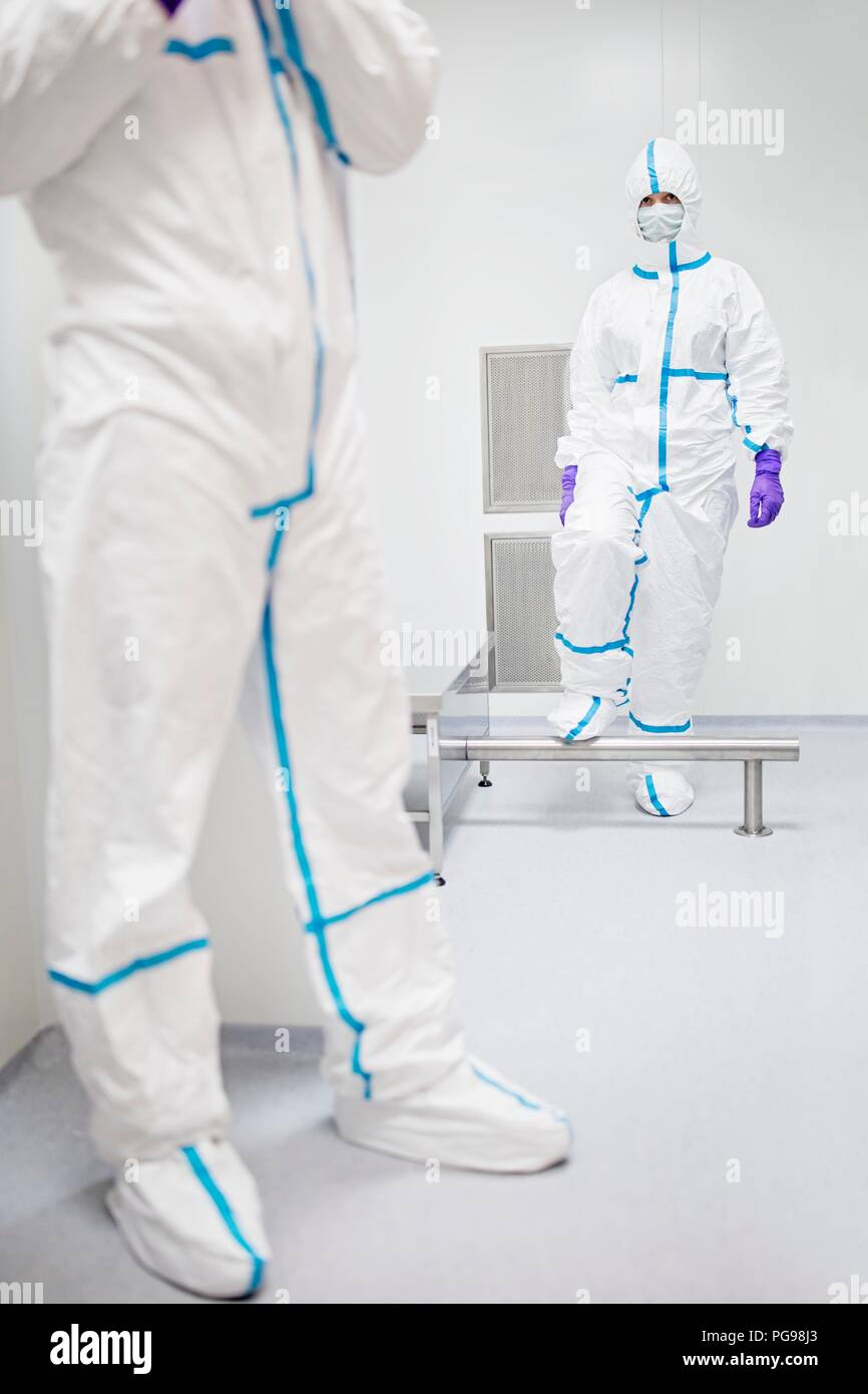 Technicians walking through a decontamination cabin before entering a sterile laboratory. - Stock Image