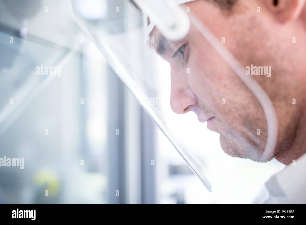 Lab technician wearing a face shield. - Stock Image