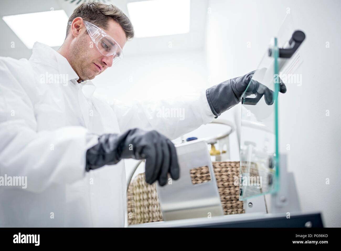 Technician storing stem cell samples in cryostorage. They have been frozen in liquid nitrogen to preserve them. Stem cells are a potential source of cells to repair damaged tissue in diseases such as Parkinson's and insulin-dependent diabetes. Stock Photo